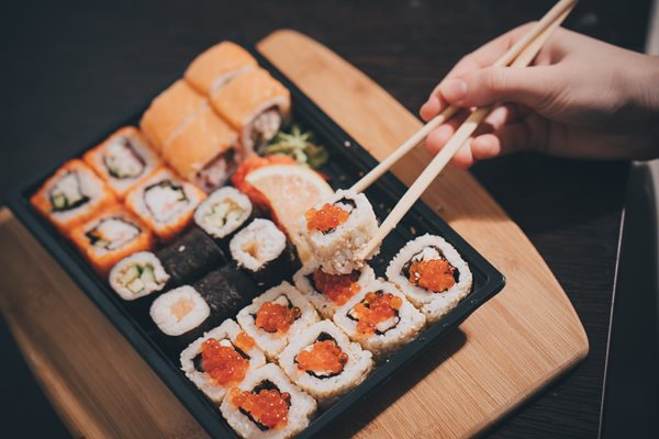 Set-sushi-set-Hand-with-chopsticks-for-sushi-_shutterstock_527851219.jpg